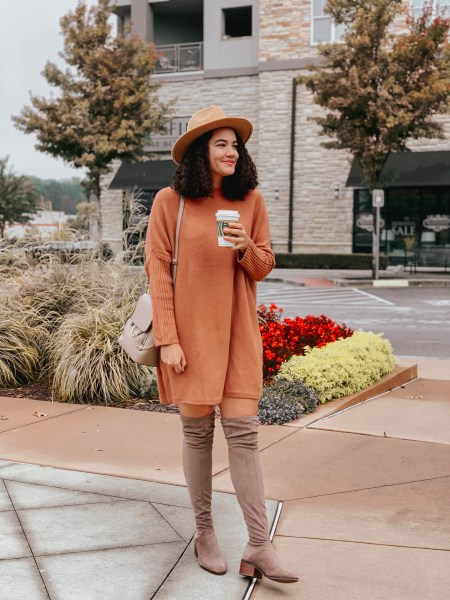 Girl with curly hair wearing an orange sweater dress, taupe over the knee boots, a tan panama hat, and a taupe ring crossbody bag