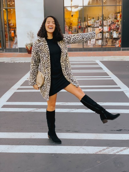 Girl with curly hair wearing a black dress, a leopard print jacket, black boots, and a taupe clutch.