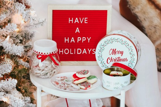 """A holiday spread of christmas cookies, a letterboard that says """"have a happy holidays"""", and chocolate covered pretzels."""