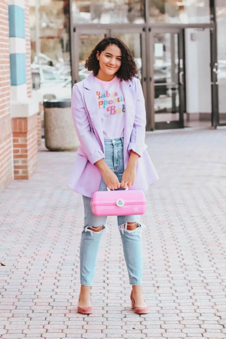 """Girl with curly hair wearing a purple blazer, a graphic tee that says """"babes supporting babes,"""" busted knee mom jeans, pink velvet block heels, and carrying a caboodle."""