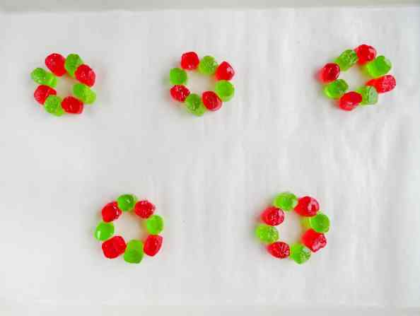 halved red and green jolly rancher candies arranged in a circle on white paper