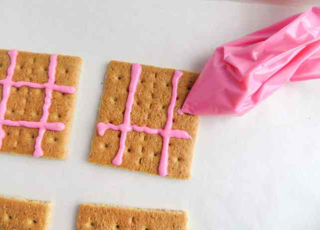 piping pink frosting on graham crackers on a white background