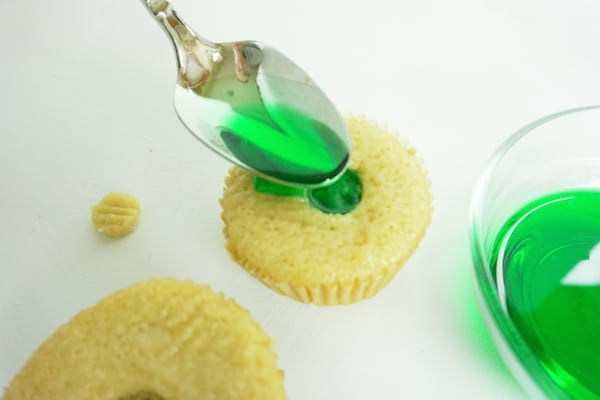 spoon filling a well in a cupcake with green liqueur mixture