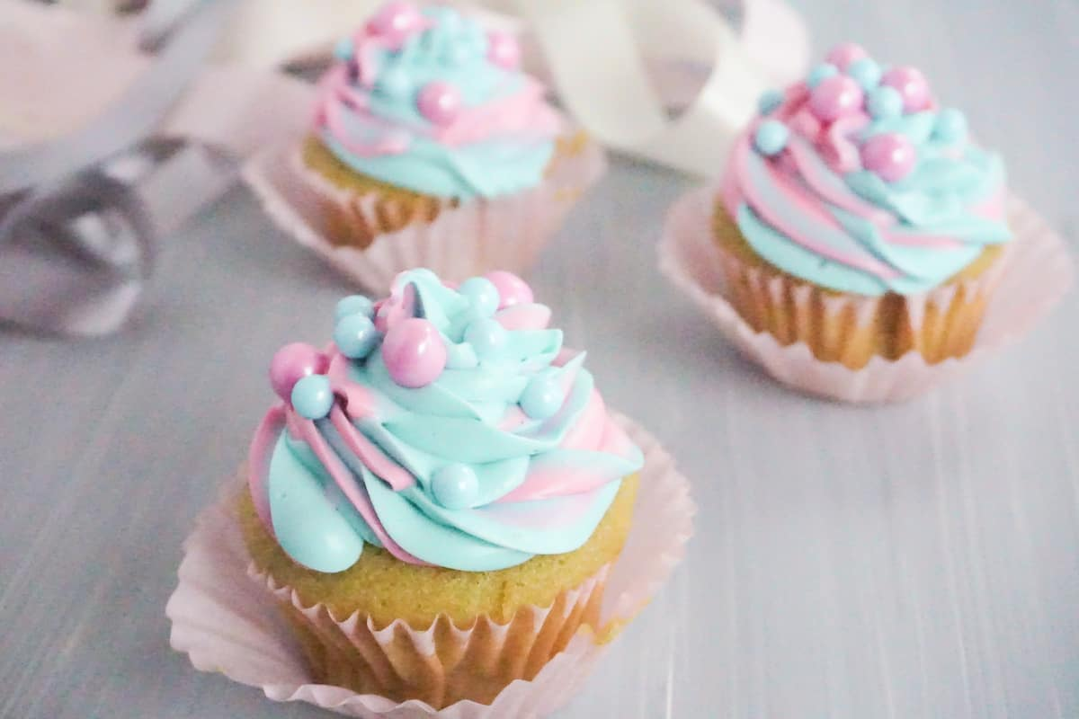 side view of three cupcakes with pink and blue swirled frosting with pink and blue large sugar pearls on a grey table with white pink and grey ribbons in the background