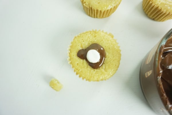 chocolate oozing out of the top of a cupcake around a mini-marshmallow stuffed into a well in the cupcake with more cupcakes and a bowl of melted chocolate on a white table in the background