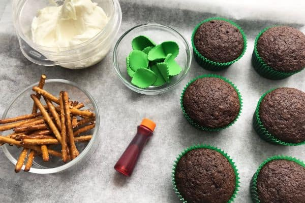white frosting in a bowl, Orange gel food coloring, pretzel sticks in a glass bowl, Wilton candy leaves in a glass bowl, chocolate cupcakes, all on parchment paper