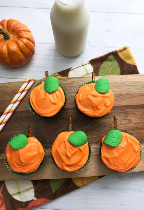 cupcakes decorated with orange frosting, green candy leaf, and pretzel stem to look like pumpkins on a wood slat next to two straws with a pumpkin and  a glass of milk in the background
