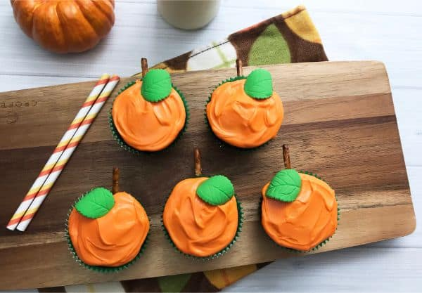 chocolate cupcakes decorated with orange frosting, a green leaf, pretzel stem to look like pumpkins on a wood slate on a white wood table with straws and a pumpkin in the background