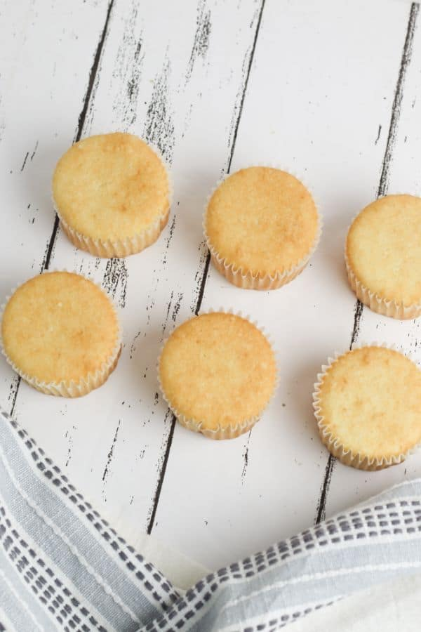 white cupcakes on a white wood table with a gray linen next to them