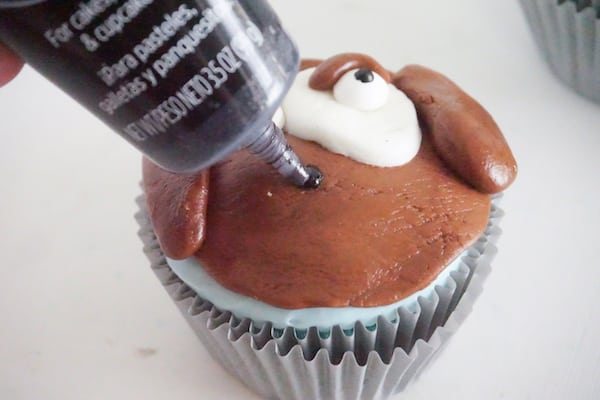 black writing gel being used to draw a mouth on a cupcake decorated with brown and white fondant to look like a dog