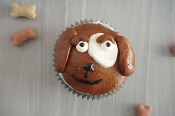 cupcake topped with brown, white and block frosting to look like the face of a dog next to dog bone treats on a table