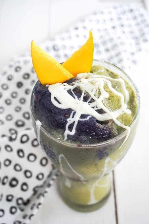 Mermaid frappucino in a glass cup tipped with white cream and 2 slices of mango with a black and white cloth on a table