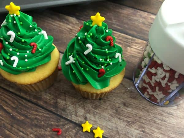 Two green cupcakes with green frosting in the shape of a Christmas tree with candy cane sprinkles and a star on top, and sprinkles in a container in the background.