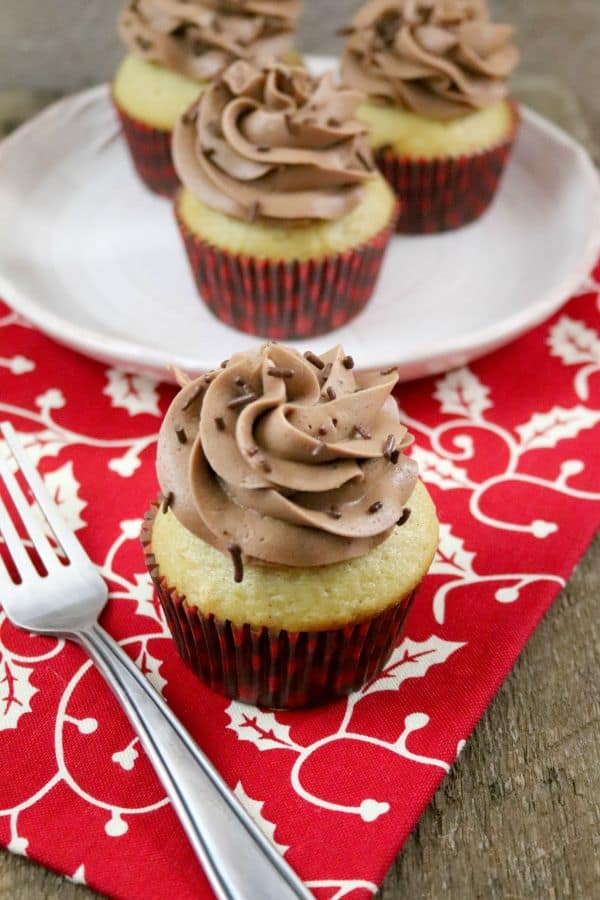 Eggnog cupcake with chocolate frosting and chocolate sprinkles with more cupcakes on a white plate in the background, a fork in the foreground, all on a red and white napkin.