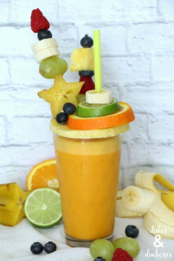 freakshake extreme smoothie in a glass topped with fruit slices and skewers with a white brick background