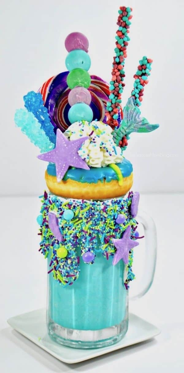 mermaid freakshake by The Soccer Mom Blog in a glass topped with blue and green candy and a blue frosted donut