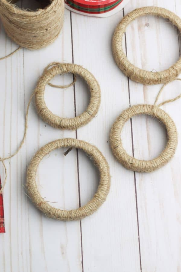 mason jar lid rings wrapped in twine next to a ball of twine and a roll of red and green ribbon on a white wood table