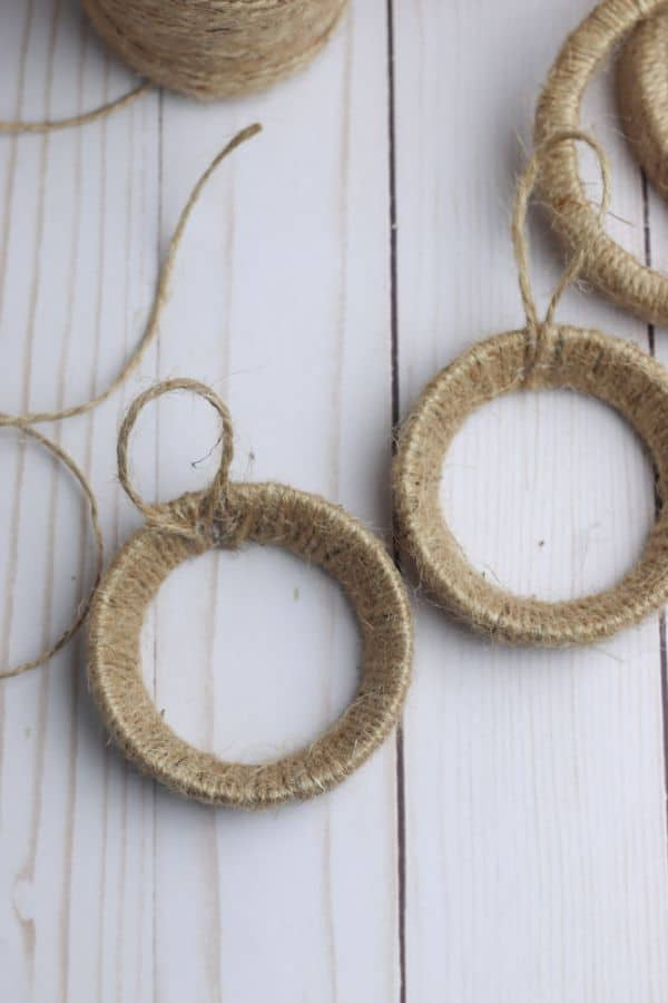 mason jar lid rings wrapped in twine next to a ball of twine on a white wood table