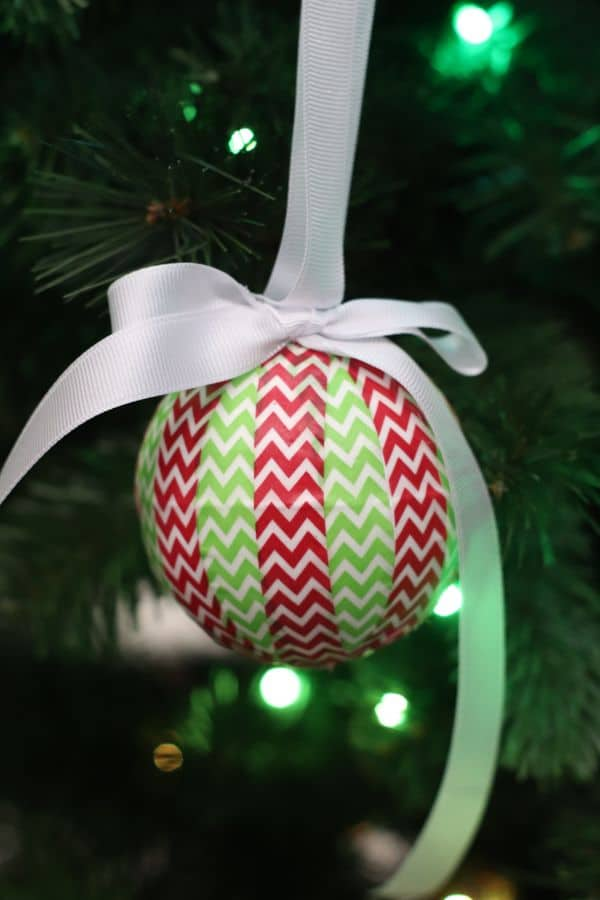 on ornament wrapped with red and green washi tape hung with a white ribbon from a Christmas tree