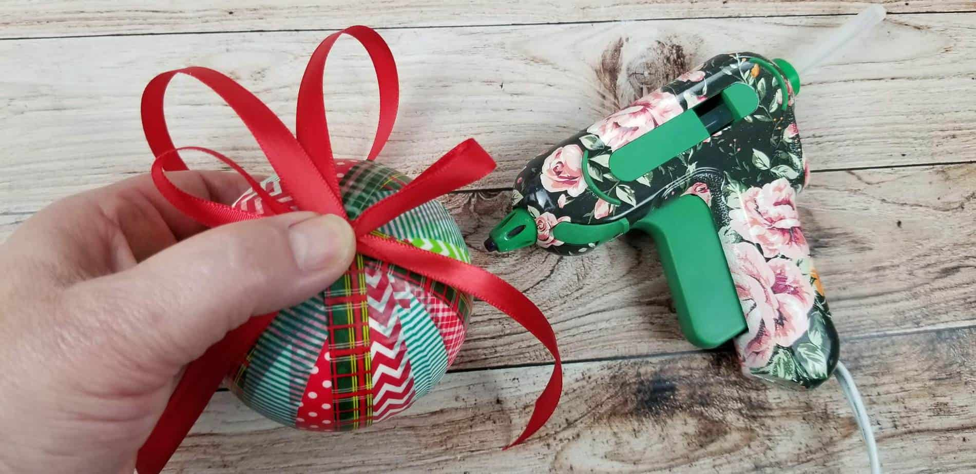 a hand holding red ribbon at the top of an ornament wrapped in washi tape on a wooden table next to a glue gun