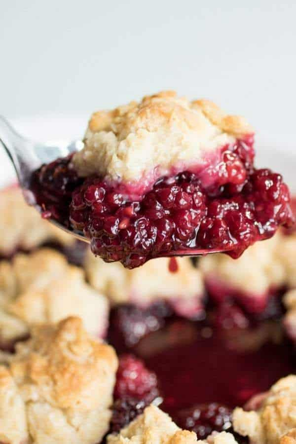 a scoop of grandmas blackberry cobbler on a spoon above the rest of the cobbler