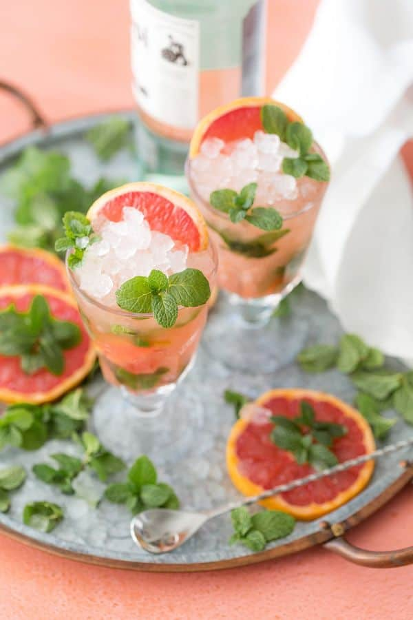 grapefruit mojito in two glasses topped with grapefruit slices and greenery with more of the same on the gray tray