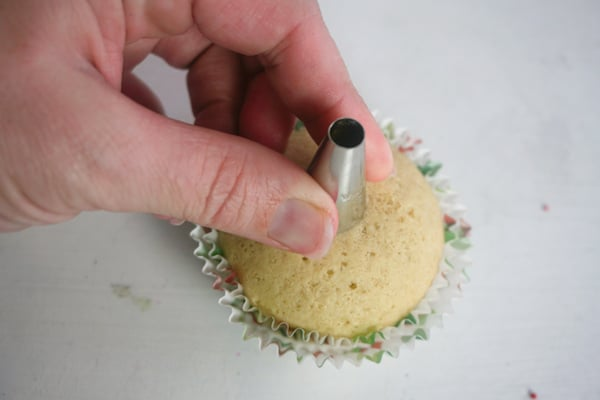 a hand holding a decorating tip over a cupcake