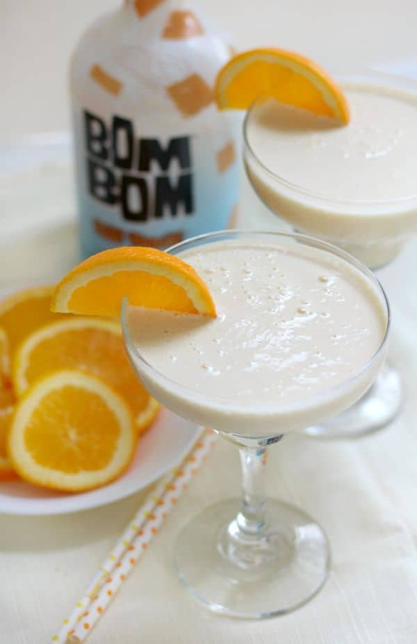 two glasses of orange julius cocktail topped with an orange slice with more orange slices on a white plate and a bottle of bom bom next to them on a white linen