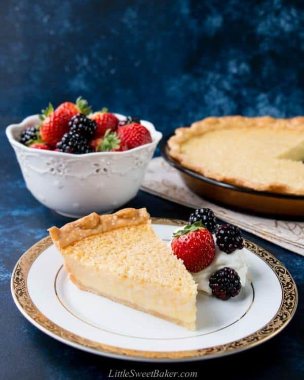 southern buttermilk pie on a white and gold plate next to a strawberry and blackberries with more of the fruit in a white bowl and the rest of the pie in the background