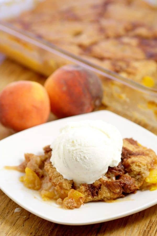 southern peach cobbler topped with vanilla ice cream on a white plate next to two peaches