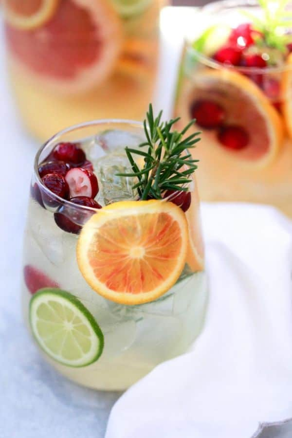 winter white sangria in glasses with a slice of orange and lime in it, with some berries and greenery on a gray counter