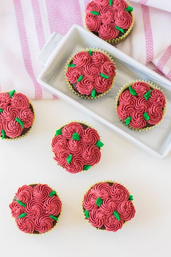 an overhead view of chocolate cupcakes decorated with red frosting to look like roses and green frosting for the stems on a white table with more cupcakes and a pink and white cloth in the background