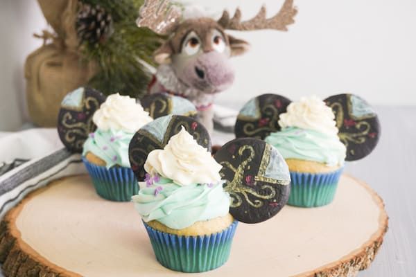 cupcakes decorated with green ans white frosting and decorated cookies to look like Princess Anna Mickey Ears cupcakes on a log