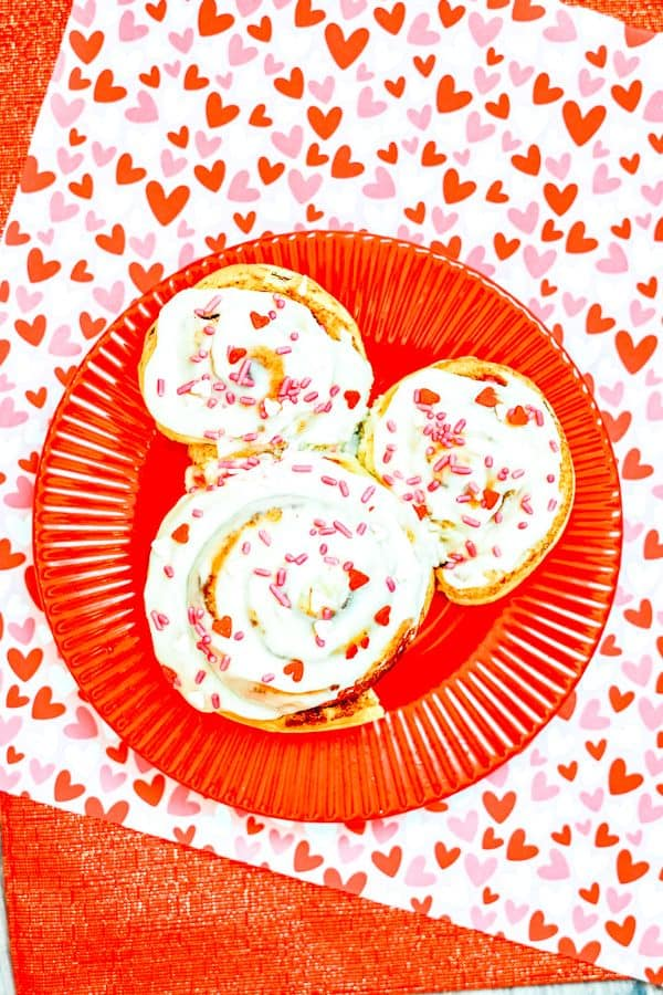 cinnamon rolls put together in the shape of mickey mouse decorated with white frosting, and red and pink sprinkles on a red plate on a pink and red heart paper