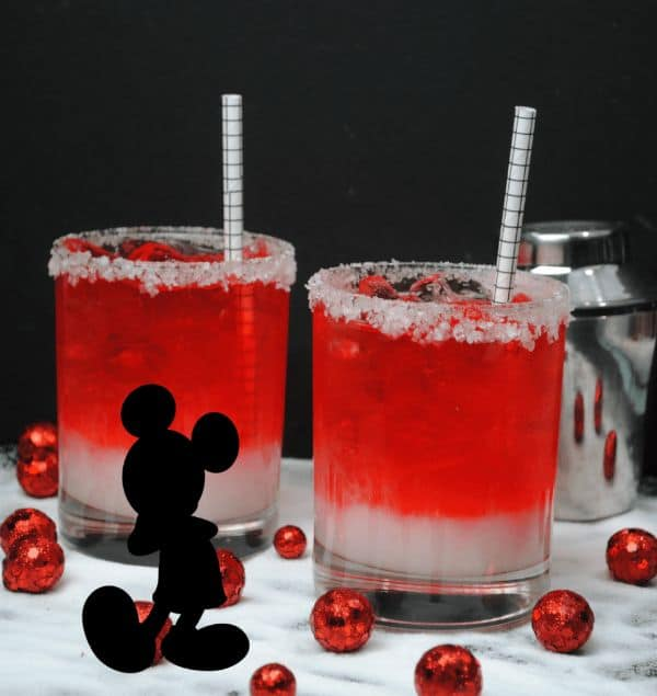 mickey mouse cocktail in two glasses with straws in them on a white counter with red metal balls around the glasses with a black mickey mouse graphic in the forefront