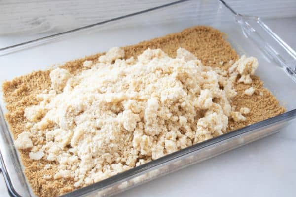 graham cracker crumbs in a glass baking dish topped with a crumble mixture on a white counter