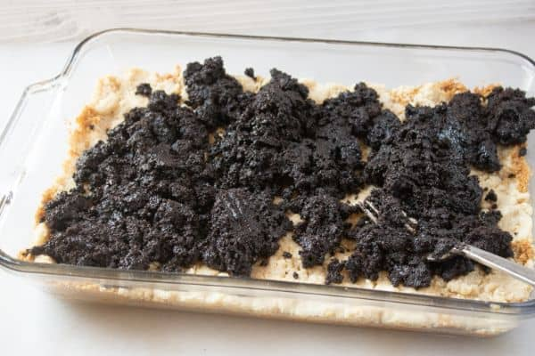 graham cracker crumbs in a glass baking dish topped with a crumble mixture and oreo cookie mixture on a white counter