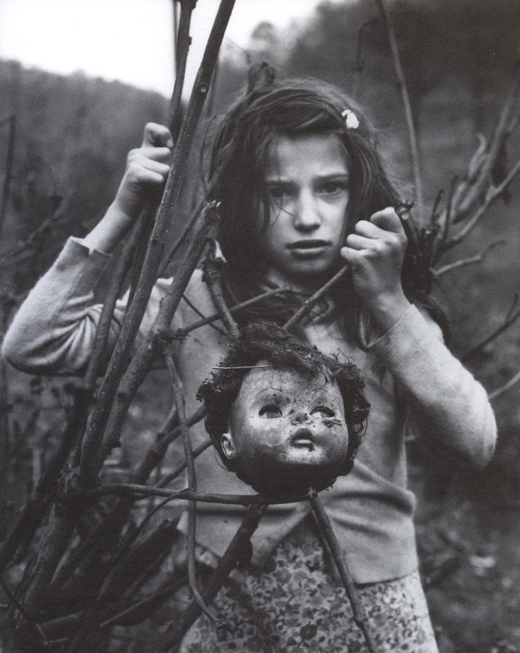 15 - 1968. Girl with doll head, West Virginia, by Arthur Tress.