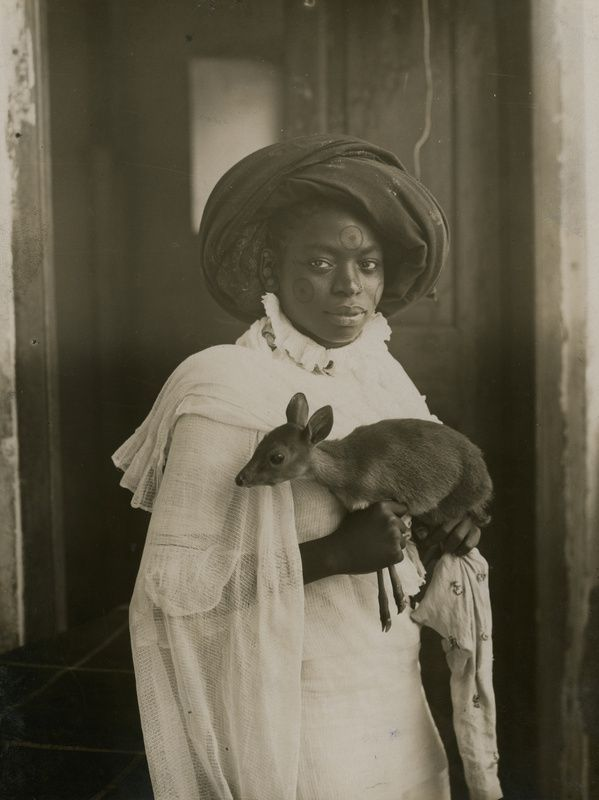 21 - c. 1909. A Kenyan woman holds her pet antelope in Mombassa.