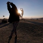 """Rochelle Schieck dances by the """"Truth is Beauty"""" sculpture at the 2013 Burning Man arts and music festival in the Black Rock desert of Nevada"""