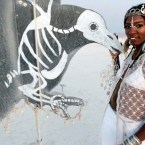 Burning Man participant Virginia Biney from Philadelphia poses next to an art installation at the 2013 Burning Man arts and music festival in the Black Rock desert of Nevada