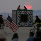 Participants watch the sunrise from atop an art installation during the Burning Man 2013 arts and music festival in the Black Rock Desert of Nevada