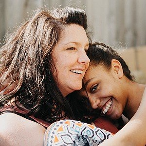 Mom and adopted teen daugheter loving each other and smiling | Serenity Links Coaching: Professional life coaching services for moms of adopted and foster children