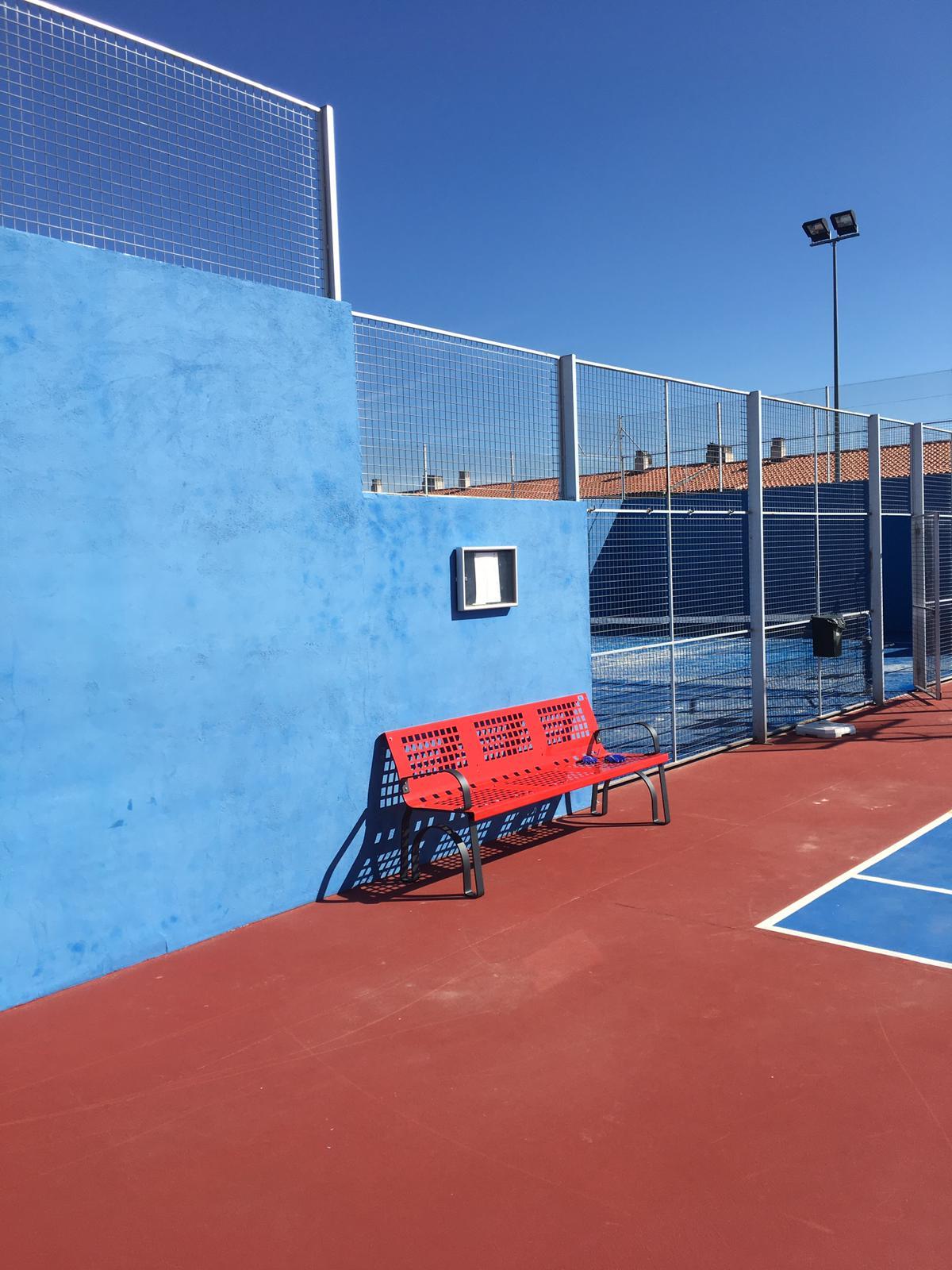 banco rojo en pista de tenis