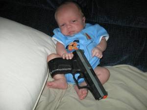 This is not a good baby with a gun. This is a thug holding a gun gangsta-style, which seems impossible since gangsta rap ended 20 years before he was born.