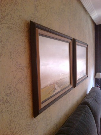 Detalle de papel pintado y cuadros en la pared del sofa