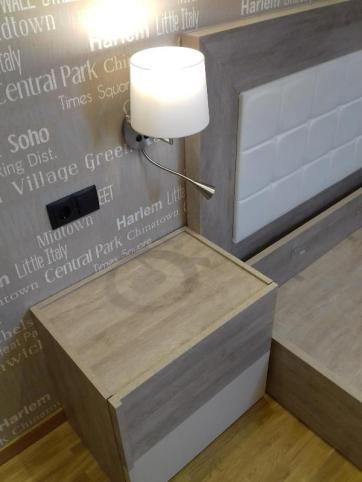 Detalle papel pintado Caselio mesita de noche y aplique de luz con lector instalado en la pared