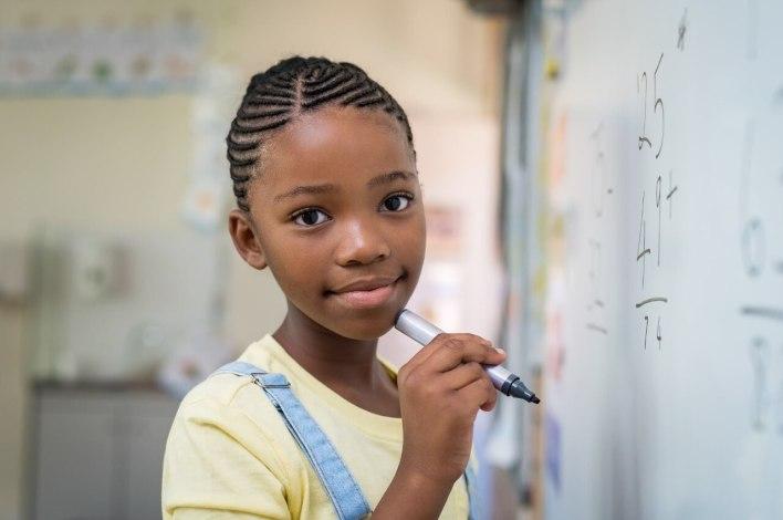 Menina, em uma sala de aula, segurando uma caneta em frente ao quadro, olhando para a câmera.