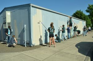 Volunteers paint the mobile classroom at Periwinkle