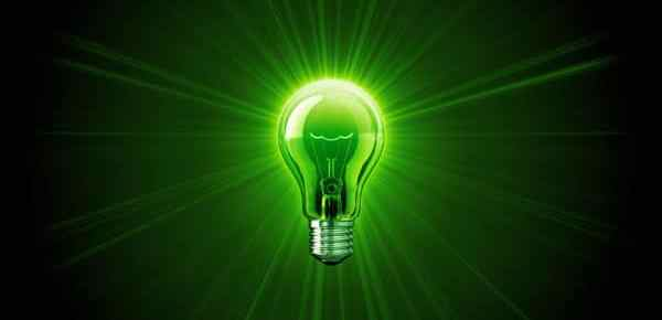 green incandescent light bulb illuminating green background with rays of light